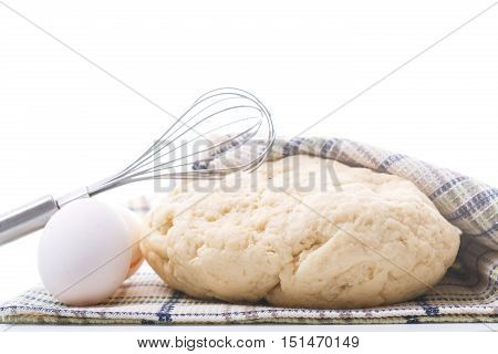 yeast dough raw eggs and whisk on a white background