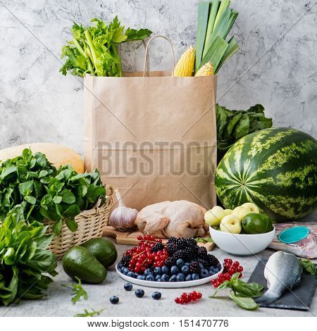 Shopping paper bag with fresh vegetables, fruits, fish, poultry and meat on the kitchen table.
