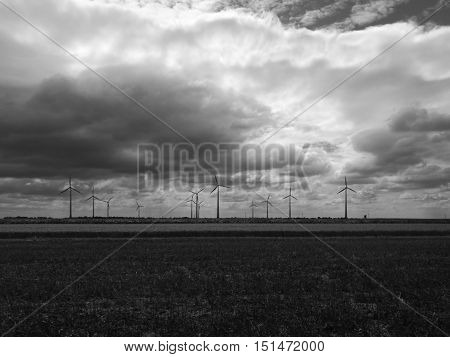 Windmill powerplant silhouette in black and white landscape