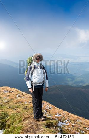 Female hiker standing on mountain on hiking trek. Side view of woman in warm clothing carrying backpack. Woman is enjoying idyllic view of mountain landscape.