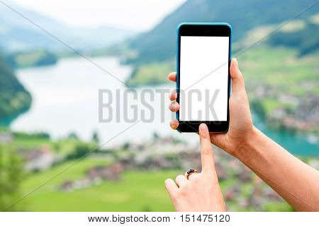 Phone with white screen to copy paste on the landscape background in Switzerland