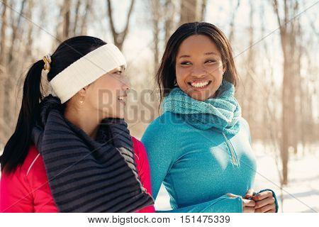 Diverse duo of millenial young adult friends take a break while training for cross-country running in the wintertime in a snow-filled park