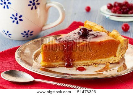 Homemade pumpkin pie with red currant jam and cranberries on red napkin.