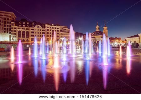 Musical fountain with colorful illumination at night with reflection. Ukraine, Kiev. Travel entartainment sightseeing background