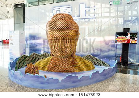 HONG KONG - NOVEMBER 03, 2015: Buddha sculpture made of Tuna salad cans at Hong Kong Airport. Hong Kong International Airport is the main airport in Hong Kong.