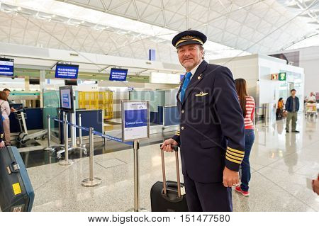 HONG KONG - NOVEMBER 03, 2015: indoor portrait of a pilot in Hong Kong Airport. Hong Kong International Airport is the main airport in Hong Kong. It is located on the island of Chek Lap Kok.