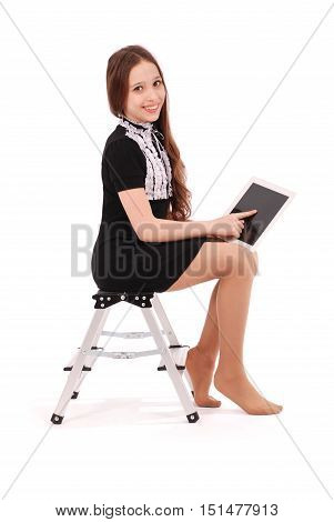 Happy student teenage girl sitting sideways on the ladder with tablet pc isolated on white