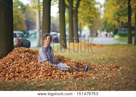 a Young girl throwing autumn leaves in the air lying on the ground in a big pile of fallen leaves.
