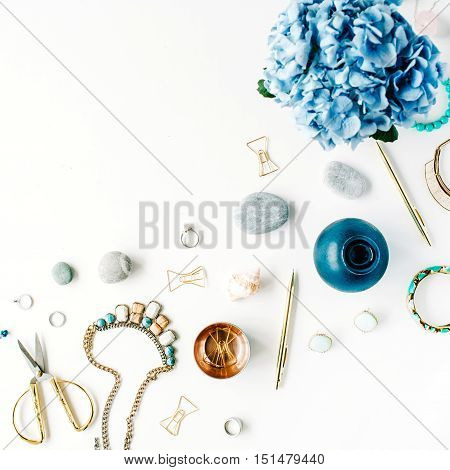 hydrangea feminine accessories golden clips and pen on white background. top view