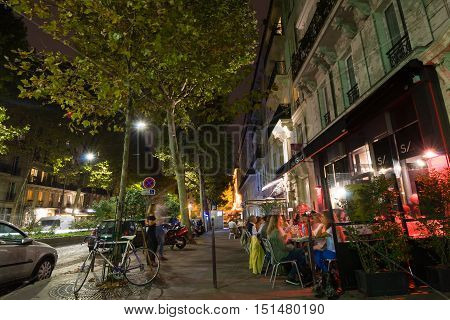 Paris By Night. The People Sit And Talk In A Cafe.