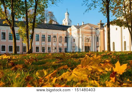 Veliky Novgorod Kremlin park with Clock Tower of St Sophia Cathedral and fallen autumn leaves on the foreground in Novgorod Russia. Focus at the clock tower. Architecture autumn landscape