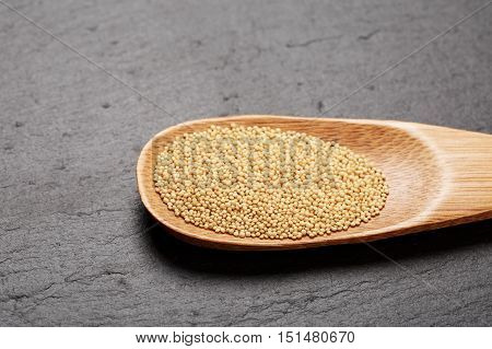 Raw white amaranth seeds in wooden spoon on black stone background. Concept of healthy and gluten free food.