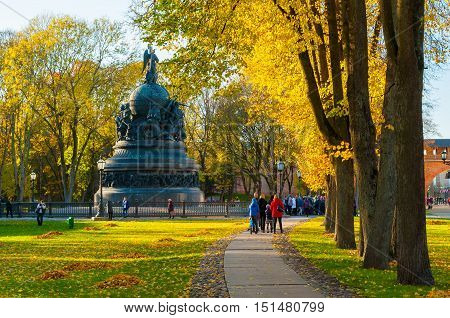 VELIKY NOVGOROD RUSSIA - OCTOBER 9 2016. The bronze monument Millennium of Russia in autumn sunset and people walking in the autumn park in Veliky Novgorod Russia