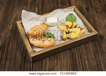 Fried fish in batter served with potatoes and tartar sauce in a wooden box on a paper