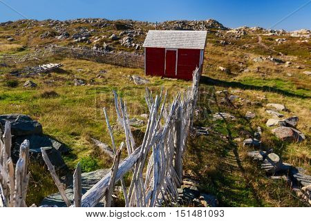 A rocky field with a traditional wooden enclosure in rural Newfoundland, Canada.