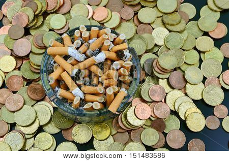Buying cigarettes lose money and health . cigarette, money and ashtray.
