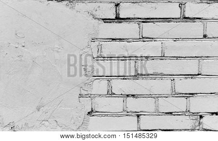 Fragment of gray brick wall painted and at left covered with cement.