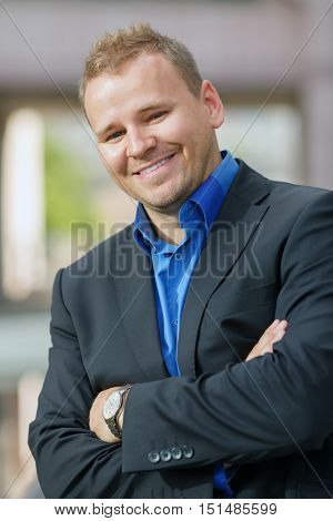 half growth portrait of handsome young businessman in black jacket walking outdoors, smile
