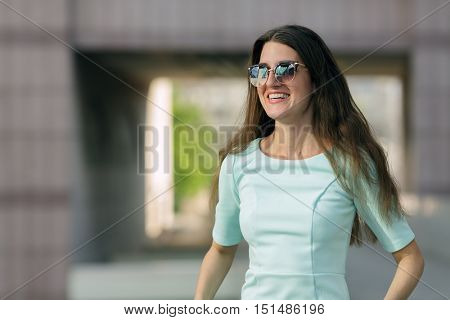 Close-up portrait of beautiful young fashion model in sunglasses posing in city street, smiling