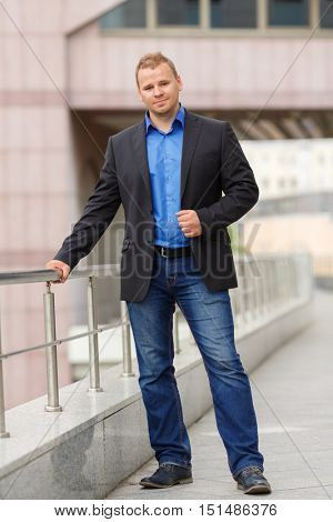 portrait of handsome young businessman in black jacket and jeans walking outdoors