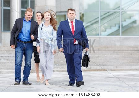 four business people (two man and two woman) walking down street on background of business centers
