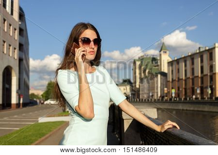 beautiful young fashion model in light green dress posing in city street, talking on phone