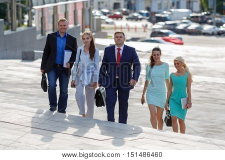 five young attractive business people climb flight of stairs in an urban environment