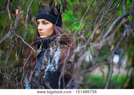 Beautiful woman in scarf and cap in the park among the bare branches of trees