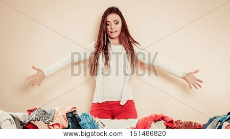 Worried Young Woman With Sofa Full Of Clothes.