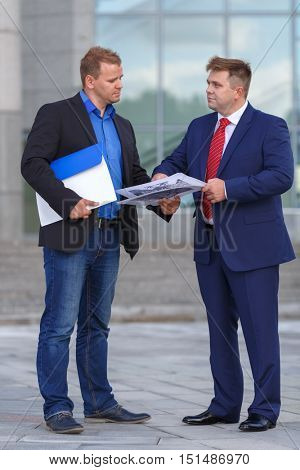 Two mature well dressed businessman outside discussing project