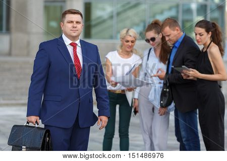 Team leader stands with four coworkers in background (two man, three woman)