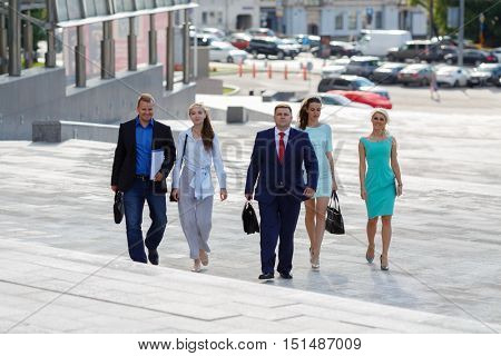 five young attractive business people climb flight of stairs in an urban environment summer day