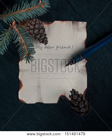 christmas, new year. a sheet of paper on a desk with a branch of fir tree and cones. inscription - my dear friend