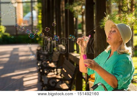 Senior lady is blowing bubbles. Woman in hat outdoors. I feel like a magician. Memories of childhood.