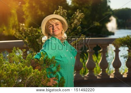 Elderly woman wearing hat. Lady on background of nature. Beautiful place beside a lake. Granny's vacation in summer.
