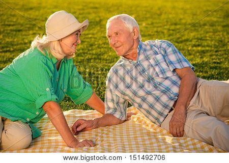 Couple on meadow is smiling. Senior man beside woman. We're happy to be together. Two halves of a whole.