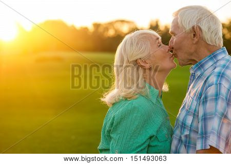 Senior couple is kissing. Man with woman outdoor. Best husband in the world. Love and tenderness.
