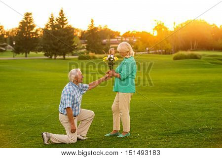 Man giving flowers to woman. Senior couple on green meadow. Heart of the gentleman. Accept this modest gift.