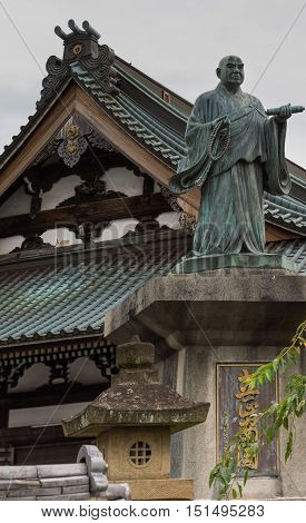 Kyoto Japan - September 15 2016: Statue of the monk Nichii who founded this Myoden-ji Buddhist Temple in Kyoto. Background is roof structure of the temple.