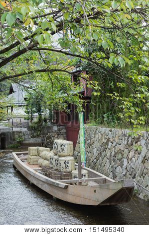 Kyoto Japan - September 15 2016: Replica of historic flat bottomed river boat in canal of Kyoto. Set under green tree cover. Loaded with Sake bags and other merchandise.