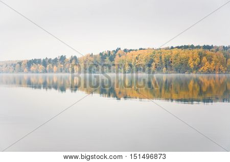 Fog on the lake Senezh in Solnechnogorsk fall in calm weather. Autumn water landscape