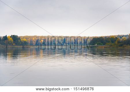 Fog on the lake Senezh in Solnechnogorsk fall in calm weather. The view of the pedestrian bridge. Autumn water landscape
