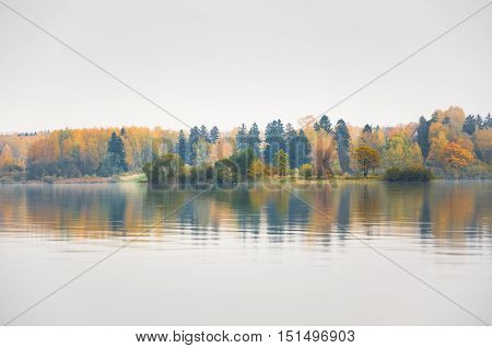 The island of lovers on lake Senezh in Solnechnogorsk fall in the fog in calm weather. Autumn water landscape