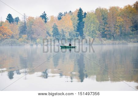 Fishing on the lake Senezh in Solnechnogorsk in the fall. The fog, the wind, the silhouette of a fisherman in a boat. Autumn water landscape