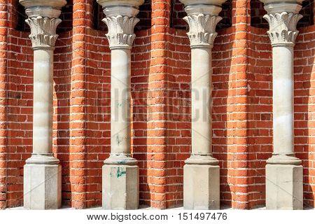 Four Corinthian Columns On A Brick Wall Of A Church