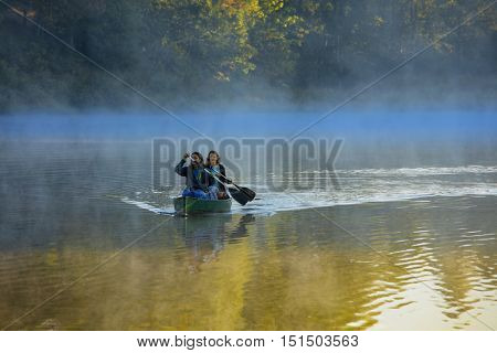 Mother and daughter canoeing in morning mist