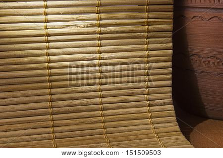 Napkin bamboo and earthen jar on a wooden background