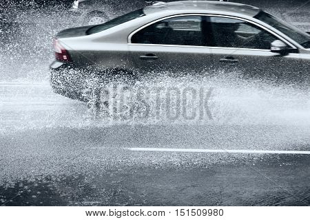 Flooded Road With Rain Puddles And With Riding Cars Splashing Water From The Wheels