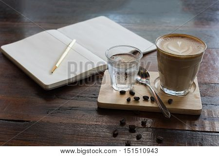 hot fresh coffee in see through glass water glass wooden notebook golden pen coffee bean on wooden tray and table at coffee time / hot fresh coffee and camera