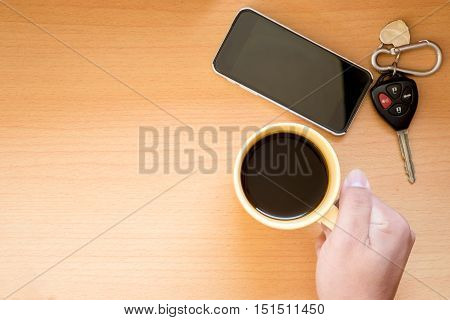 Hand holding coffee cup on wooden background with phone and car keytop view.